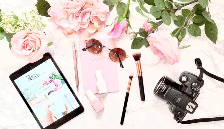 image shows a flat lay style photo of my iPad, some pink flowers, sunglasses and my canon camera.