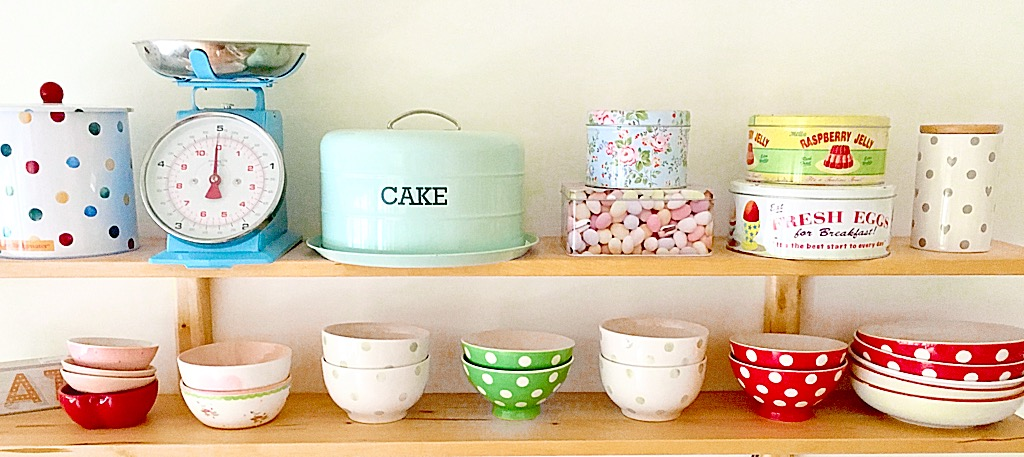 a shelf full of baking tins and bowls