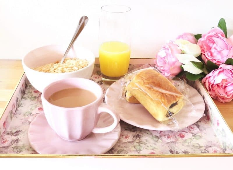 image shows a continental breakfast on a floral tray.