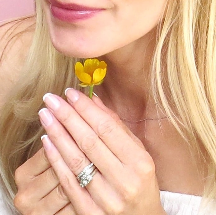 Samantha holding a buttercup to her chin showing the baby French manicure.
