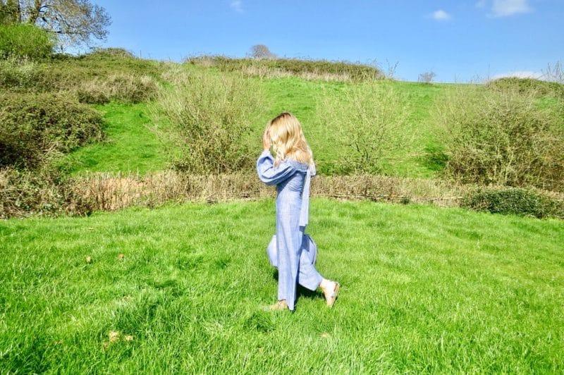 Samantha walking through a field wearing an asos jumpsuit.