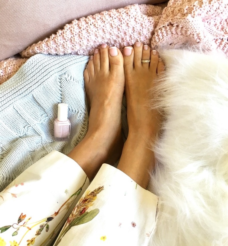 samantha's feet showing French manicured toes on the bed.