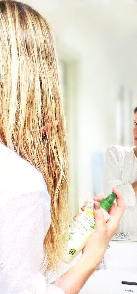 Samantha spraying the leave in conditioner into her wet hair.