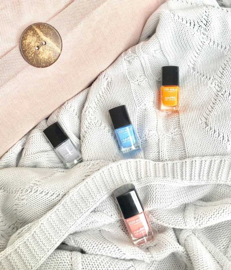 Itsy polishes scattered on a blanket.