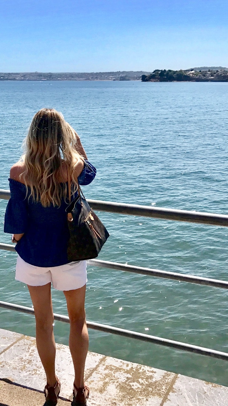 Image shows Samantha looking out to sea wearing white shorts and off shoulder denim top